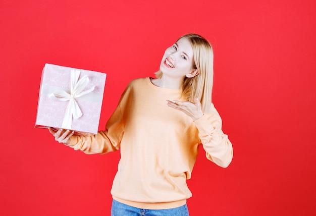 Belle blonde femme pointant le coffret cadeau qui tient dans sa main droite devant le mur rouge