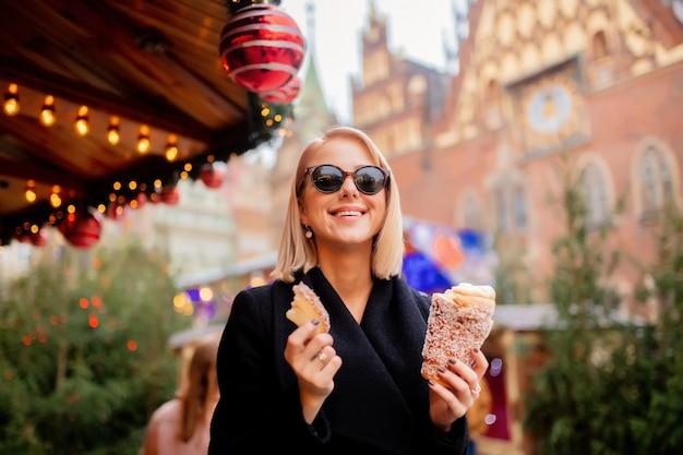 Belle blonde avec un gâteau à la broche au marché de noël à wroclaw, en pologne