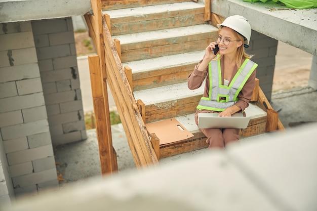 Belle blonde heureuse ingénieur civil caucasien dans un gilet réfléchissant ayant une conversation téléphonique à l'extérieur