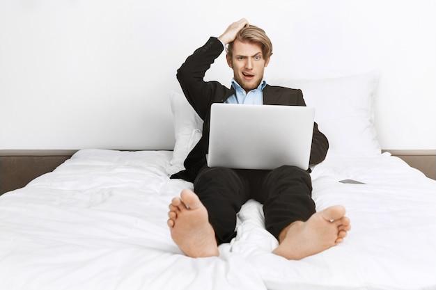 Belle blonde homme d'affaires non rasé couché dans son lit, travaillant sur un ordinateur portable, tenant la main sur la tête avec une expression choquée après avoir fait une erreur de calcul.