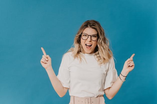 Une belle blonde hurlante à lunettes vêtue d'une blouse blanche et d'un pantalon rose clair avec une ceinture se dresse sur un fond bleu pointé par l'index vers le haut. concept de vente et de remise.