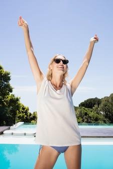 Belle blonde levant les mains debout au bord de la piscine