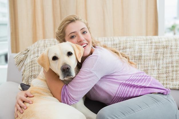 Belle blonde se détendre sur le canapé avec chien
