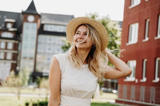 Une belle blonde se promène dans une ville européenne. femme en robe blanche et chapeau de paille, elle sourit et est heureuse