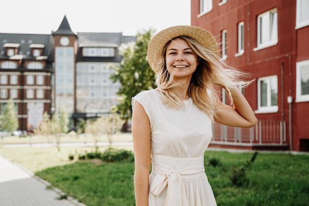 Une belle blonde se promène dans une ville. femme en robe blanche et chapeau de paille