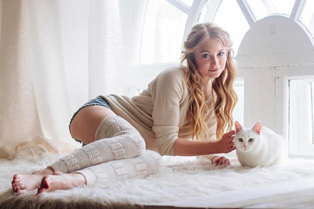 Belle blonde sexy assise dans la fenêtre le long du chat