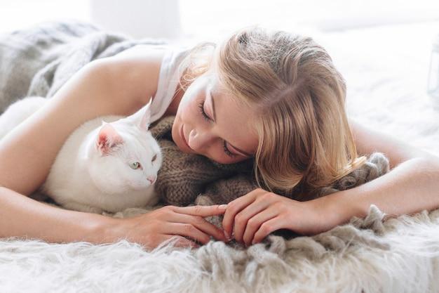 Belle blonde sexy se trouve sur la fenêtre avec un chat
