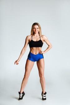 Une belle blonde en short de sport et un haut pose sur un fond blanc, montrant un corps en relief.