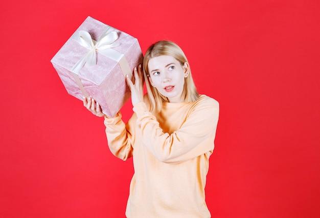 Une belle blonde soulève la boîte-cadeau et l'écoute devant le mur rouge