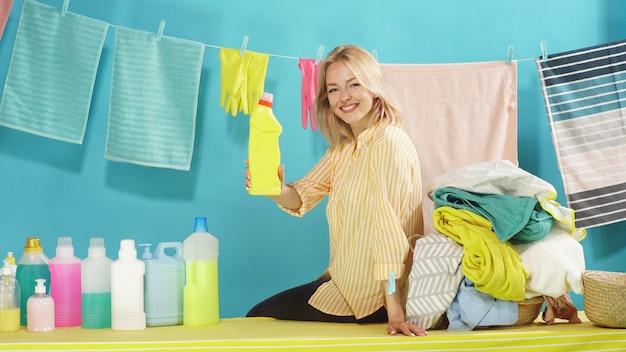 Belle blonde souriante détergents professionnels de la publicité sur un mur bleu isolé