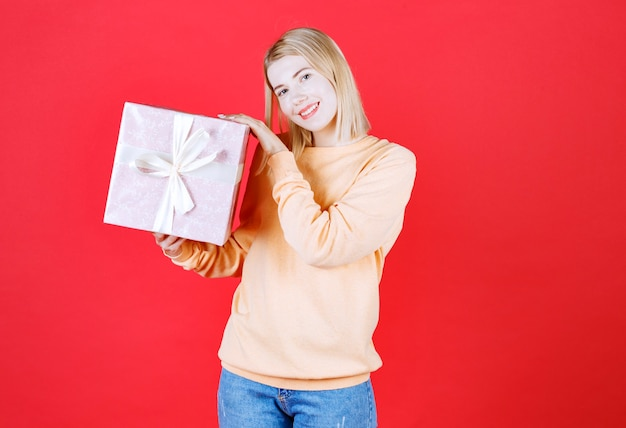 Belle blonde tenant la boîte-cadeau dans son côté droit devant le mur rouge