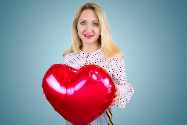 Une belle blonde tient un ballon en forme de cœur dans ses mains