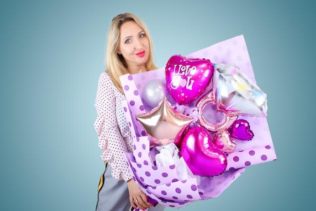 Une belle blonde tient dans ses mains un bouquet de ballons en forme de cœur sur lequel l'inscription je t'aime