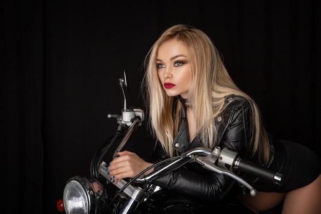 Belle blonde en veste de cuir noir assise sur une moto