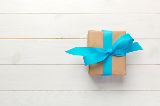 Belle boîte-cadeau avec un arc bleu sur la table en bois blanche, vue de dessus
