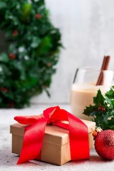 Belle boîte cadeau en or avec un arc rouge et des rubans, une boule, des branches de lait de poule et de baies de houx sur la table en pierre. noël et nouvel an