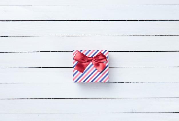 Belle boîte cadeau présente sur fond de bois blanc