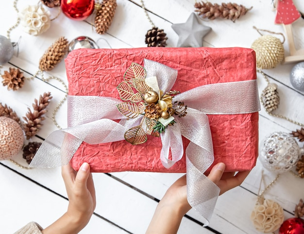 Belle boîte cadeau rose dans les mains contre les détails du décor de noël se bouchent.
