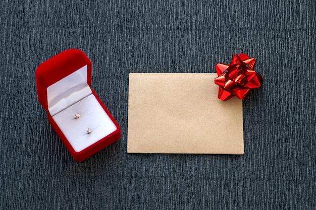 Belle boîte rouge avec des boucles d'oreille et une enveloppe avec un arc