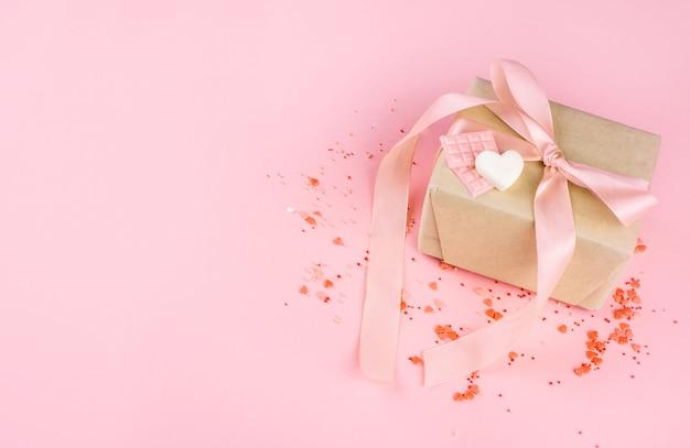 Belle boîte avec ruban en satin, avec petits coeurs, coeurs en chocolat au chocolat au lait.