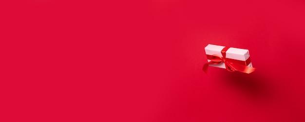 Belle boîte surprise enveloppée dans du papier rose d'emballage et un ruban noeud de ruban de satin rouge plane dans l'air sur un fond rouge
