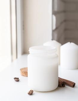 Belle bougie blanche avec des bâtons de cannelle et des grains de café sur une surface blanche