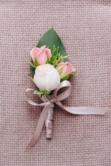 Belle boutonnière de marié classique avec de belles roses isolées sur fond texturé rose