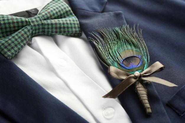 Belle boutonnière avec plume sur costume pour le marié, gros plan