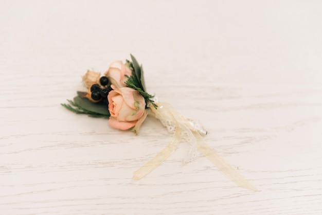 Belle boutonnière avec une rose dans un style rustique se trouve sur un fond blanc, copiez l'espace