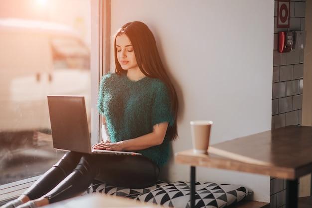 Belle brune à l'aide d'un ordinateur portable au café