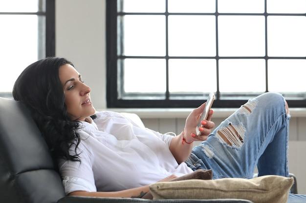 Belle brune à l'aide de smartphone à la maison