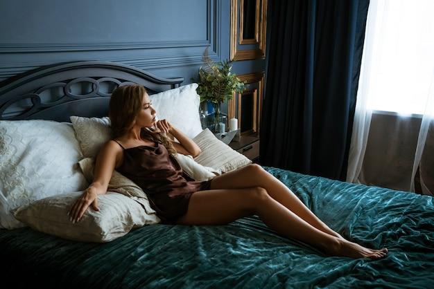 Belle brune allongée sur le lit, photo sombre
