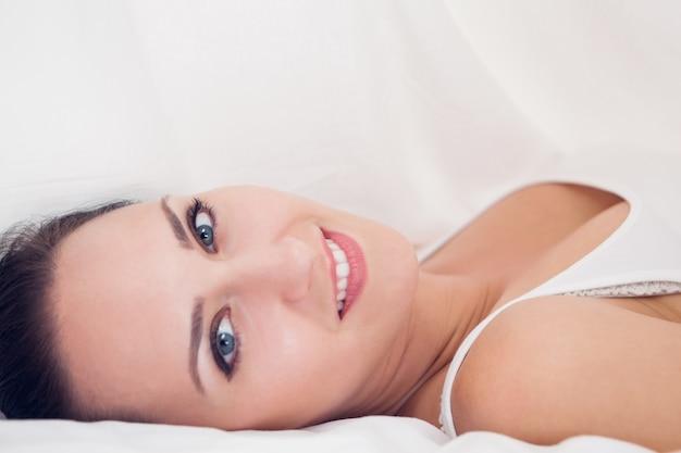 Belle brune allongée sous les draps en regardant la caméra