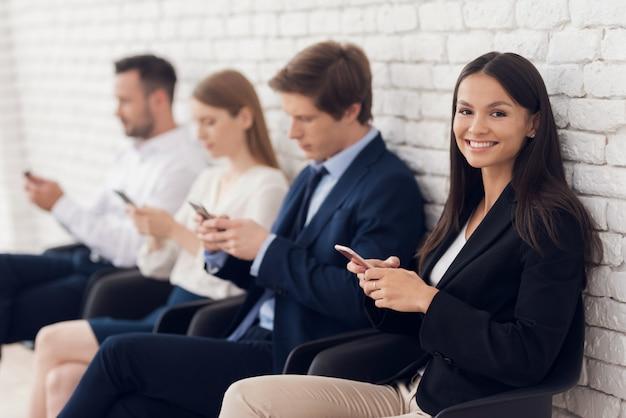 Belle brune assise à la réception avec smartphone.