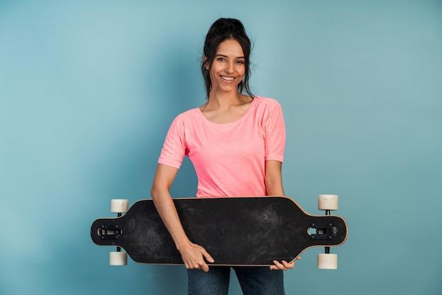 Belle brune attrayante avec un patin. positif jeune femme posant