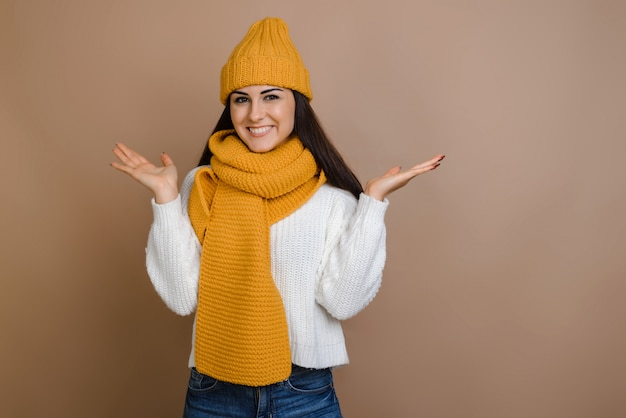 Belle brune au chapeau chaud et mitaines sur fond marron étalant les bras.