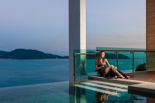 Belle brune aux cheveux bouclés dans une belle robe de soirée en chocolat posant avec un verre à la main et une bouteille de champagne près de la piscine
