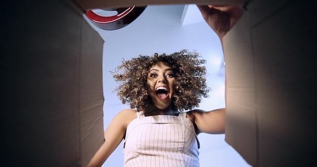 Belle brune aux cheveux bouclés ouvrant la boîte avec votre commande reçue par la poste ou la société de messagerie. jeune femme brésilienne recevant l'ordre.