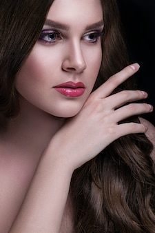 Belle brune aux cheveux longs et maquillage pose