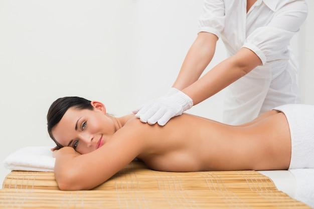 Belle brune bénéficiant d'un massage du dos exfoliant