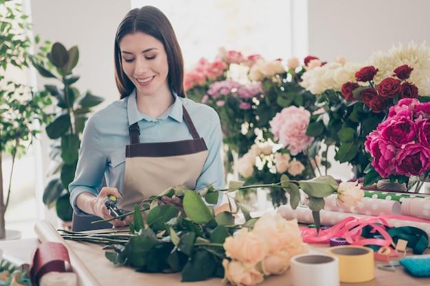 Belle brune botaniste posant dans son magasin de fleurs