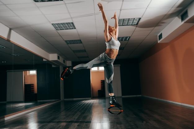 Belle brune caucasienne en tenue de sport sautant sur des chaussures de sauts kangoo dans la salle de gym.