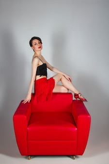 Une belle brune en chaussures rouges est assise dans un fauteuil rouge sur fond gris.