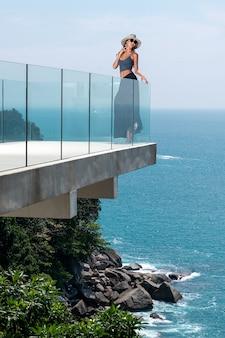 Une belle brune avec un corps mince dans un chapeau pose sur la terrasse extérieure en verre de son hôtel