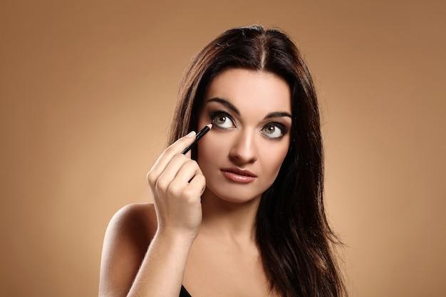 Belle brune avec un crayon de maquillage