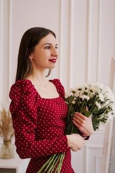 Belle brune dans une robe rouge avec un bouquet de marguerites à la maison