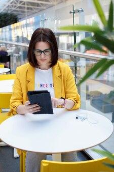 Belle brune dans une veste jaune travaillant sur une tablette numérique