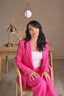 Belle brune élégante et confiante dans un intérieur moderne assis sur une chaise en fuchsia à la mode
