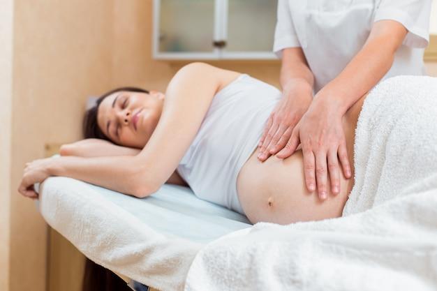 Une belle brune enceinte aux cheveux longs se trouve sur le côté lors d'une réception avec un massothérapeute dans une salle de cosmétologie