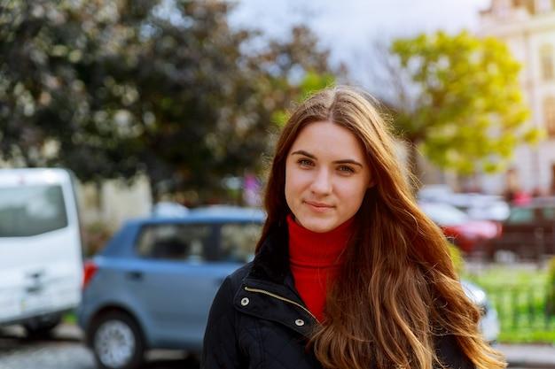 Belle brune jeune femme vêtue d'une robe et marchant dans la rue